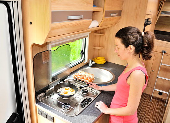 woman cooking at stove in motorhome